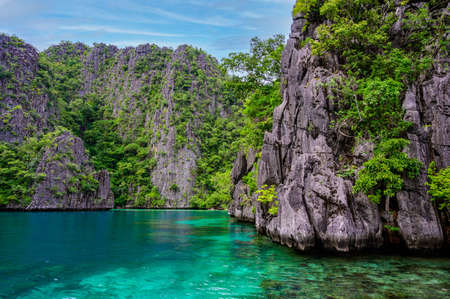 Blue crystal water in paradise Bay with boats on the wooden pier at Kayangan Lake in Coron island, tropical travel destination - Palawan, Philippines.