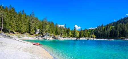 Small island in the middle of Cauma Lake (Caumasee) with crystal blue water in beautiful mountain landscape scenery at Flims, Graubuenden - Switzerland