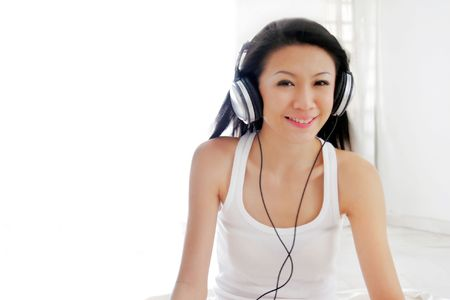 spacing: Young Asian Female Wearing Headphones Stock Photo