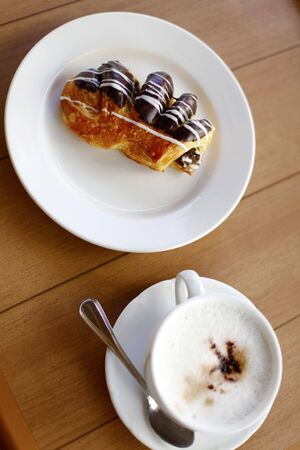 Cup of Cappuccino Coffee and a Chocolate Covered Pastry photo