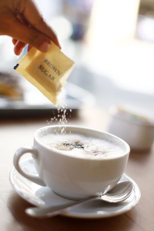 Brown Sugar being Poured into a Cup of Cappuccino photo