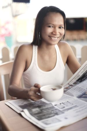thirst quenching: Young Asian Female Reading a Newspaper Over Coffee Stock Photo