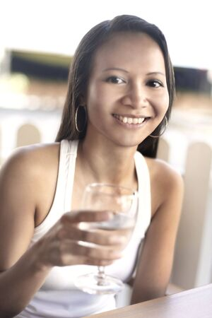 collarless: Young Asian Female Holding a Glass of Water