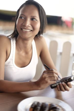 Young Asian Female Using a PDA Stock Photo - 4868278