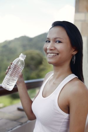 grasping: Young Asian Female Holding a Bottle of Water