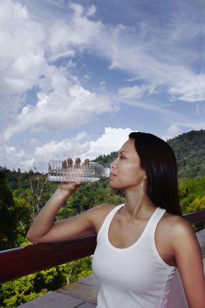 collarless: Young Asian Female Drinking from a Bottle of Water Stock Photo