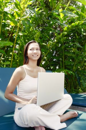 collarless: Young Asian Female Sitting on a Reclining Chair Using a Laptop Stock Photo