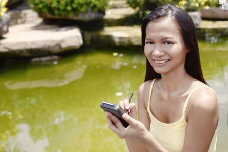 Young Asian Female Using a PDA Stock Photo - 4868277