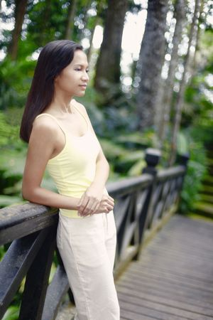 collarless: Young Asian Female Standing on a Bridge Looking Pensive Stock Photo