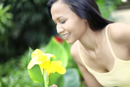 collarless: Young Asian Female Leaning to Smell a Flower