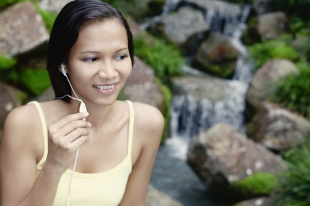 Young Asian Female Using a Mobile Phone Hands Free Set Stock Photo - 4868271