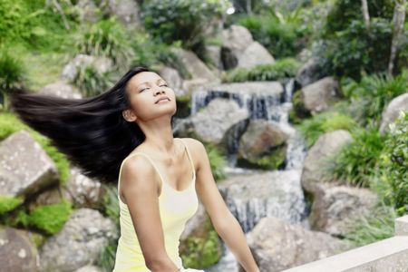 Young Asian Female Swinging her Hair by a Waterfall Stock Photo - 4868299
