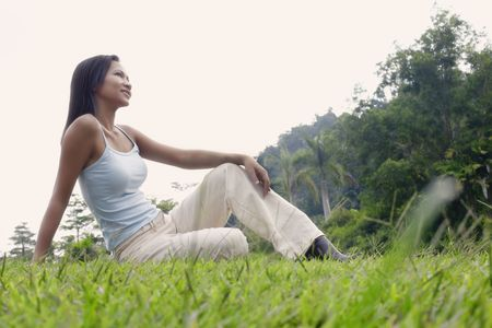 Young Asian Female Sitting on Grass and Relaxing