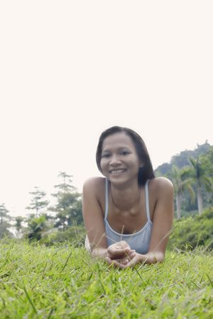 Young Asian Female Laying on Grass and Relaxing photo