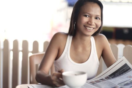 collarless: Young Asian Female Reading a Newspaper Over Coffee LANG_EVOIMAGES