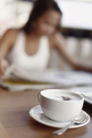 no movement: Cup of Cappuccino Coffee with Asian Female in Background