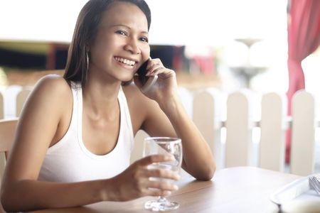 collarless: Young Asian Female Talking on a Mobile Phone