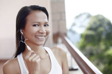 Young Asian Female Using a Mobile Phone Hands Free Set Stock Photo - 4861366