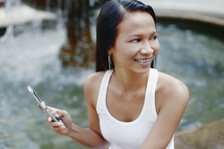 collarless: Young Asian Female Holding a Mobile Phone LANG_EVOIMAGES