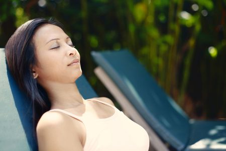 quite time: Young Asian Female Relaxing on a Reclining Chair