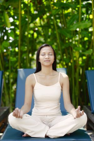 motionless: Young Asian Female Meditating on a Reclining Chair