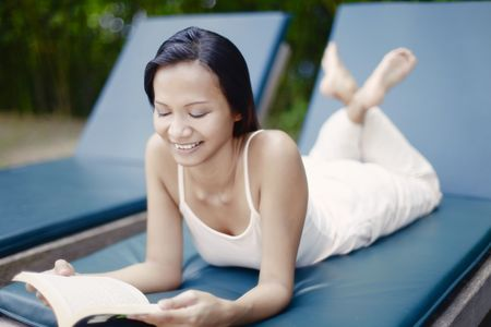 collarless: Young Asian Female Laying on a Reclining Chair Reading a Book