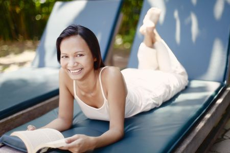 Young Asian Female Laying on a Reclining Chair Reading a Book Stock Photo - 4861370