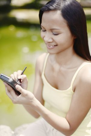 Young Asian Female Using a PDA Stock Photo - 4861362