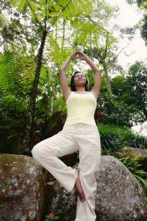 collarless: Young Asian Female Standing on a Rock and Meditating