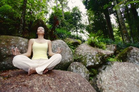 Young Asian Female Sitting on a Rock and Meditating Stock Photo