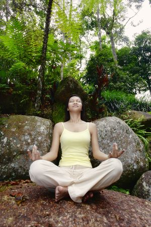 collarless: Young Asian Female Sitting on a Rock and Meditating LANG_EVOIMAGES