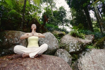 Young Asian Female Sitting on a Rock and Meditating Stock Photo - 4861397