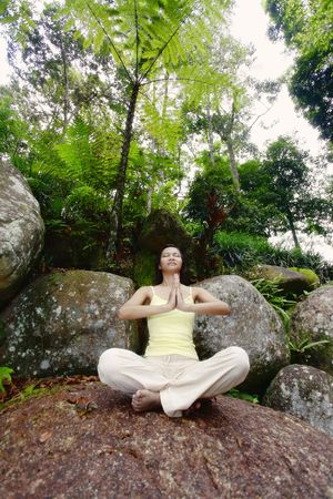 motionless: Young Asian Female Sitting on a Rock and Meditating LANG_EVOIMAGES