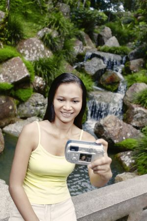 collarless: Young Asian Female Taking a Self Portrait Photo by a Waterfall
