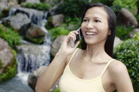 Young Asian Female Talking on a Mobile Phone Stock Photo - 4861389