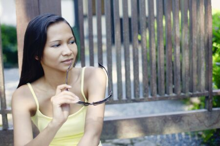 Young Asian Female Sitting by a Gate Looking Thoughtful photo