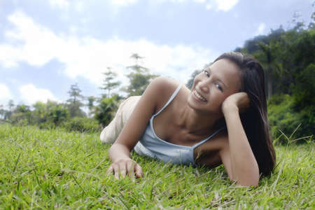 collarless: Young Asian Female Laying on Grass and Relaxing LANG_EVOIMAGES