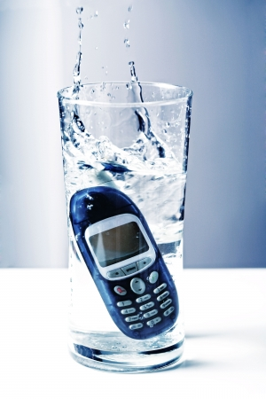 Mobile Phone Dropped into a Glass of Water Stock Photo - 5043156