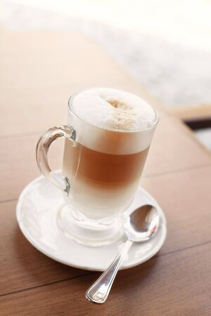 Cafe Latte in a Tall Glass on a White Saucer with a Silver Spoon