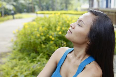 motionless: Thoughtful Young Asian Woman Relaxing in a Park