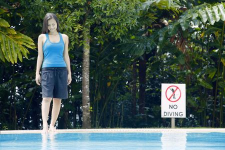 Young Asian Woman Standing Next to a Swimming Pool Stock Photo
