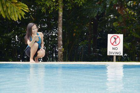 collarless: Young Asian Women Splashing Water by a Swimming Pool