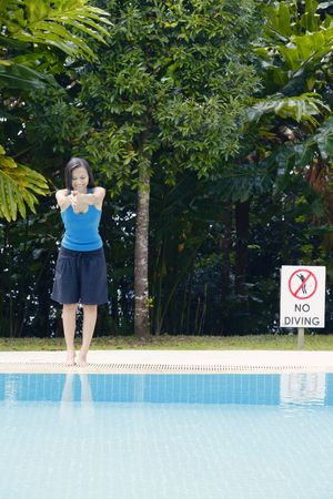 collarless: Young Asian Women Pretending to Dive into a Swimming Pool