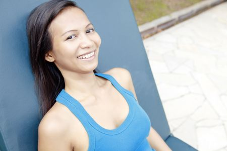 collarless: Young Asian Woman Smiling and Laying on a Sun Lounger Stock Photo