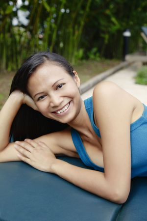 quite time: Young Asian Woman Smiling and Laying on a Sun Lounger Stock Photo