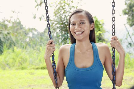quite time: Young Asian Woman Smiling and Sitting on a Swing in the Park Stock Photo