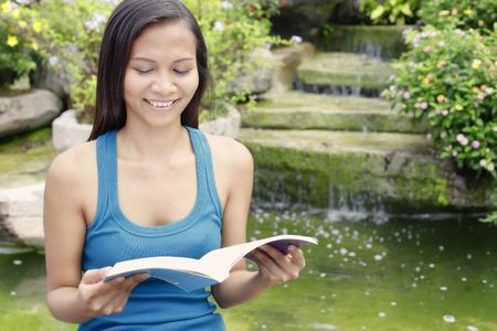 Young Asian Woman Reading a Book Next to a Water Feature Stock Photo - 6538192