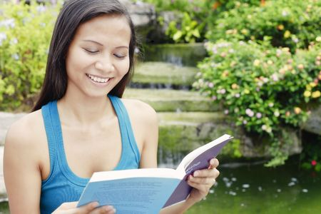 Young Asian Woman Reading a Book Next to a Water Feature