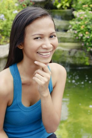 collarless: Young Asian Woman Looking Thoughtful Next to a Water Feature