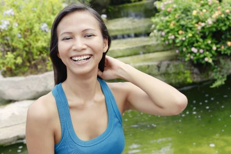 Young Asian Woman Looking Happy Next to a Water Feature